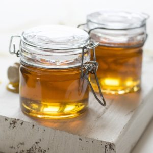 Picture of raw honey in glass jar on wooden board